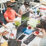 Young teamwork using virtual reality glasses in creative office - Co-workers trying new technology devices at work - Business, marketing and tech trends concept - Focus on left black man headset